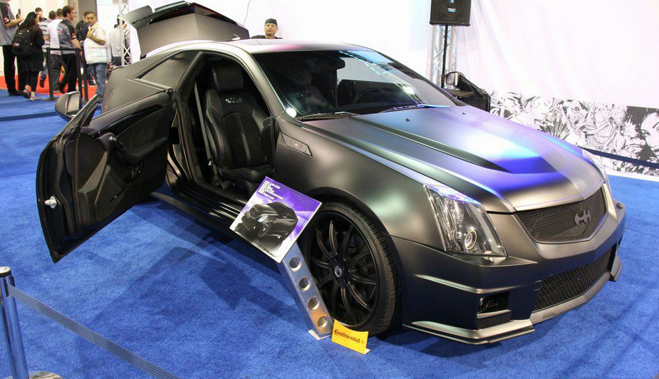 This is Justin Bieber's matte black Cadillac CTS-V coupe customized by West Coast Customs. These pictures were taken at SEMA 2011 by GT Spirit. The car has suicide doors and is wrapped in matte black vinyl. It also has a custom audio system that is no joke. It is sitting on 20″ matte black Asanti wheels which look really good on this coupe.  I was tempted to give this car a good rating but you can not take it seriously for two reasons. 1) It is a 17 year olds car. 2) It has batman logos all over and is batmobile themed. [via celebritycarz.com]