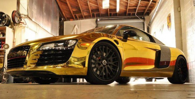 Tyga teamed up with Roadstarr Motorsports to create this gold chrome Audi R8. At first, I thought this was just a cheap vinyl wrap on the car but after I saw it in person – I realized it was actual paint! This is a very impressive car and even though it might be too loud for most people, the quality is there.  Love to see people take chances with their cars and Tyga did just that. He got a lot of publicity from it as it is going to be featured in DUB Magazine. The wheels are staggered matte black 20″ wheels. I would have liked to see some more creativity with the wheels, no point in going conservative with the paint job thats on the car. [via celebritycarz.com]
